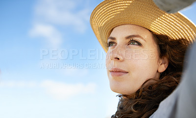 Buy stock photo Shot of a young woman wearing a sunhat and looking up at the sky on a summer's day