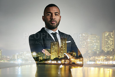 Buy stock photo Cropped portrait of a handsome young businessman standing with his arms folded superimposed against a city background