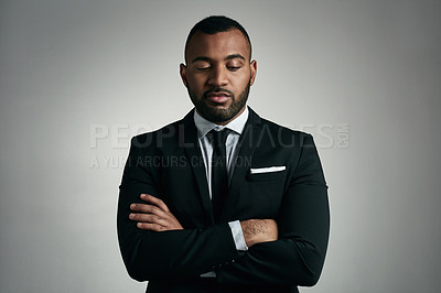 Buy stock photo Cropped shot of a handsome young businessman standing with his arms folded against a gray background