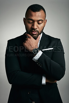 Buy stock photo Cropped shot of a handsome young businessman standing with his hand on his chin against a gray background