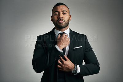 Buy stock photo Cropped portrait of a handsome young businessman adjusting his tie while against a gray background