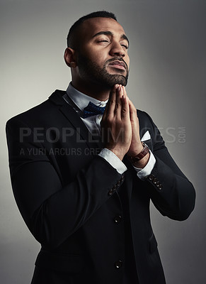 Buy stock photo Cropped shot of a handsome young businessman praying while standing against a gray background