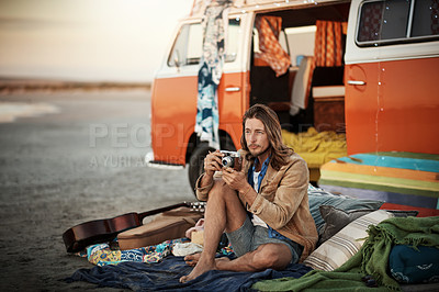 Buy stock photo Shot of a handsome young man taking a photo with his vintage camera on the beach