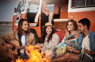 Buy stock photo Cropped shot of a group of friends sitting around a fire on the beach