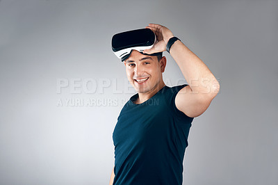 Buy stock photo Studio shot of a handsome young man posing with virtual reality goggles against a grey background