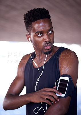 Buy stock photo Cropped shot of a handsome young man lining up his playlist while exercising out in the city