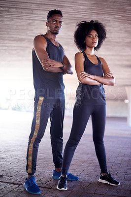 Buy stock photo Full length portrait of two young sportspeople standing with their arms crossed while working out in the city