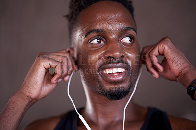 Buy stock photo Cropped shot of a handsome young man listening to music while exercising out in the city