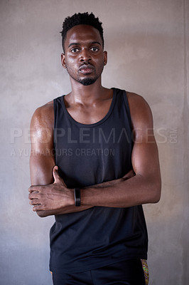 Buy stock photo Cropped portrait of a handsome and athletic young man standing outside with his arms folded