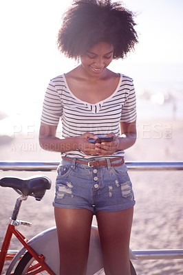 Buy stock photo Cropped shot of a young beautiful woman using a cellphone on the promenade at the beach