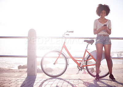 Buy stock photo Shot of a young beautiful woman using a cellphone standing next to her bicycle on the promenade at the beach