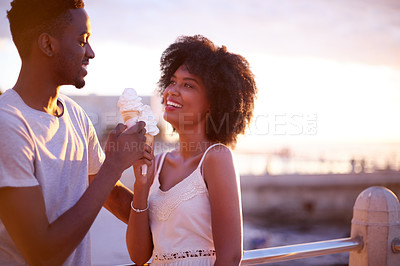 Buy stock photo Cropped shot of a young attractive couple eating ice cream while spending time together on the promenade at the beach
