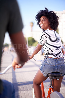 Buy stock photo Rearview shot of a young couple cycling along the promenade at the beach