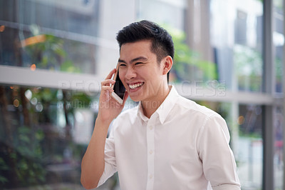Buy stock photo Shot of a cheerful young businessman talking on his cellphone while standing inside the office during the day