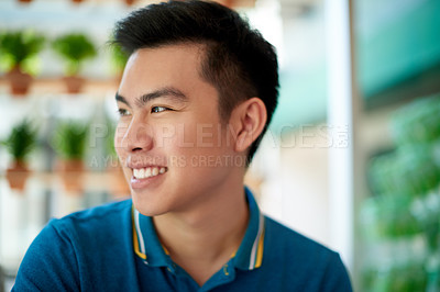 Buy stock photo Shot of a confident young man sitting at a table while looking into a certain direction and contemplating inside a cafe during the day