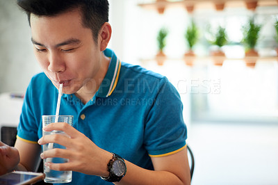 Buy stock photo Shot of a confident young man seated a table and browsing on his cellphone while drinking water inside of a cafe during the day