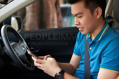 Buy stock photo Shot of a confident young man texting on his cellphone while driving in his car during the day