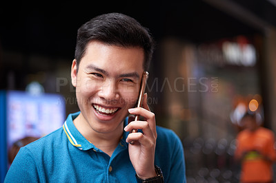 Buy stock photo Portrait of a cheerful young man talking on his cellphone while standing in the busy streets of the city during the day
