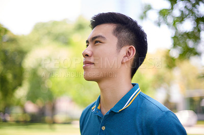Buy stock photo Shot of a confident young man standing in a park while contemplating outside during the day