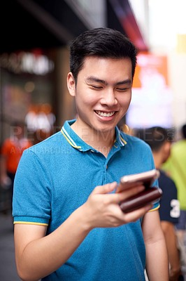 Buy stock photo Shot of a cheerful young man texting on his cellphone while standing in the busy streets of the city during the day