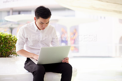 Buy stock photo Shot of a confident young man typing and working on his laptop while being seated at work during the day
