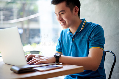 Buy stock photo Shot of a cheerful young man seated at a table while working on his laptop inside during the day
