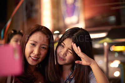 Buy stock photo Shot of two happy young women taking a selfie with a mobile phone on a night out in the city