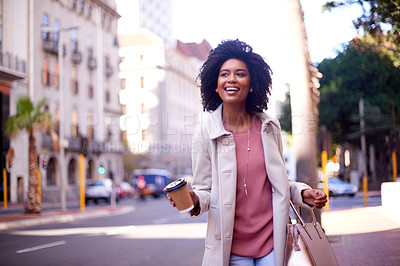 Buy stock photo Cropped shot of an attractive and fashionable young woman drinking coffee while walking in the city