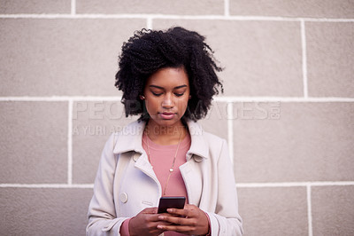 Buy stock photo Cropped shot of an attractive and fashionable young woman sending a text while out in the city