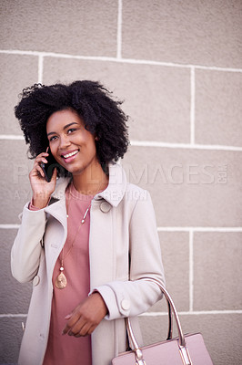 Buy stock photo Cropped shot of an attractive and fashionable young woman making a phonecall while out in the city