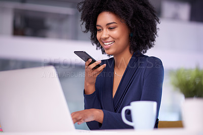 Buy stock photo Shot of a young businesswoman talking on a cellphone while working on a laptop in an office