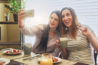 Buy stock photo Cropped shot of two young women having breakfast together in the morning at home