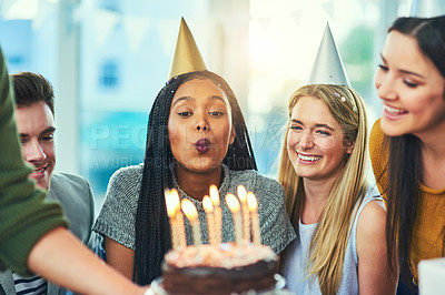 Buy stock photo Cropped shot of an attractive young woman blowing out birthday candles while surrounded by friends at her party
