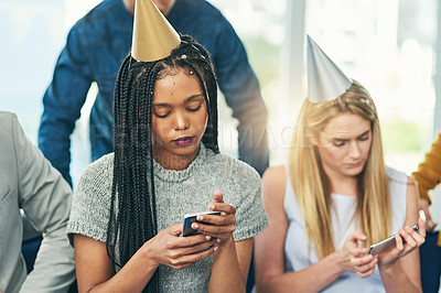 Buy stock photo Cropped shot of two young women sending text messages while celebrating a birthday with friends