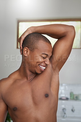 Buy stock photo Shot of a handsome young man smelling his armpit in the bathroom at home