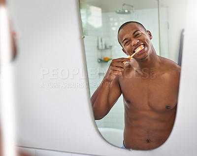 Buy stock photo Shot of a handsome young man brushing his teeth in the bathroom at home