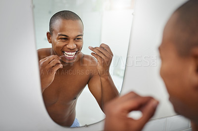 Buy stock photo Shot of a handsome young man flossing his teeth in the bathroom at home