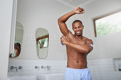 Buy stock photo Portrait of a handsome young man spraying deodorant to his armpit in the bathroom at home