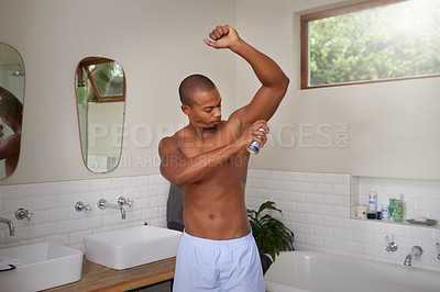 Buy stock photo Shot of a handsome young man spraying deodorant to his armpit in the bathroom at home