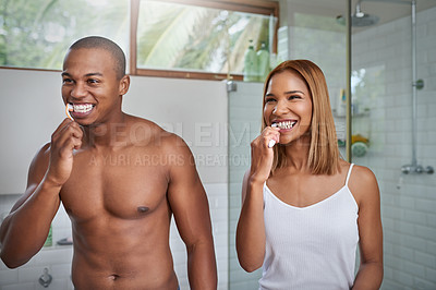 Buy stock photo Shot of a young couple brushing their teeth together in the bathroom at home