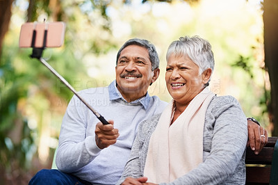 Buy stock photo Shot of a mature couple taking selfies together at the park