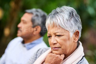 Buy stock photo Shot of a mature woman looking upset with her husband in the background