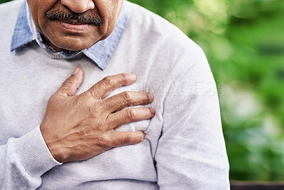 Buy stock photo Closeup shot of a mature man holding his chest in discomfort outdoors