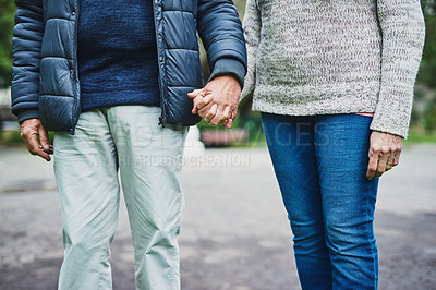 Buy stock photo Cropped shot of an affectionate senior couple holding hands in a park