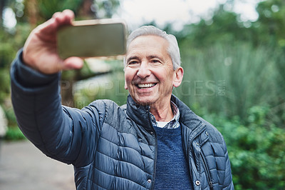 Buy stock photo Shot of a senior man taking a selfie on his mobile phone in the park