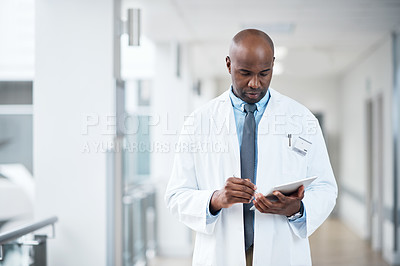 Buy stock photo Cropped shot of a handsome mature male doctor using a tablet while standing in the hospital corridor