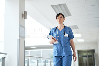 Buy stock photo Cropped shot of an attractive young female nurse walking through the hospital corridor