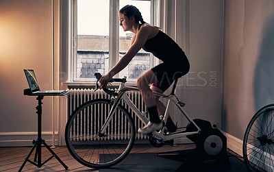 Buy stock photo Shot of a young woman working out on an exercise bike at home