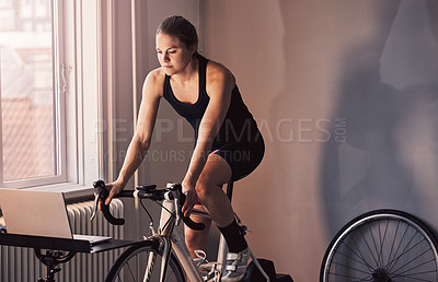 Buy stock photo Cropped shot of a young woman working out on an exercise bike at home