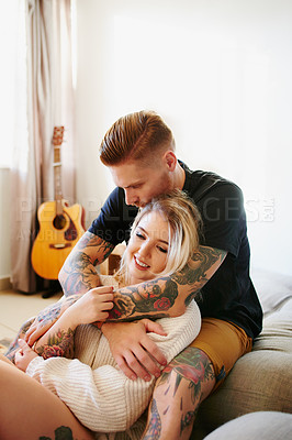 Buy stock photo Shot of an affectionate young couple relaxing together at home